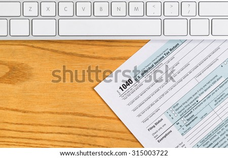 Top view of IRS Tax Revenue form with computer keyboard on desktop.  - stock photo