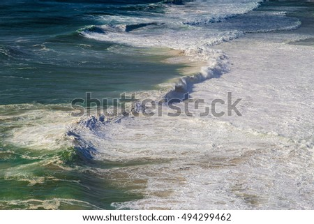 Top view of isolated emerald ocean waves with white foam, Praia do Norte, Nazare, Portugal
