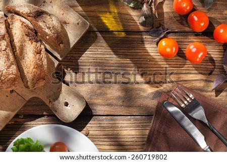 Top view of italian food on wooden table - bread, olive oil and tomatos with basil - stock photo