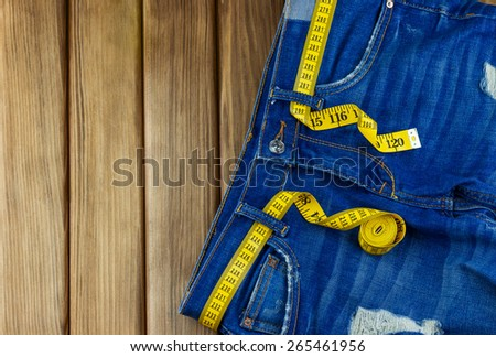 Top view of jeans with measuring tape on wooden background with place for your text - stock photo