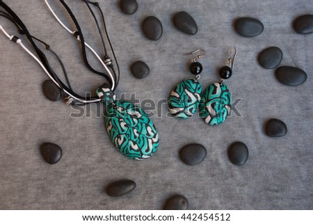 Top view of jewelry set pendant and earrings with black stones on grey fabric. Handmade jewelry of polymer clay/