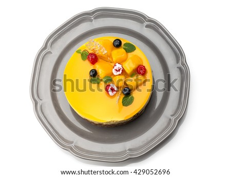 Top view of Joconde Imprime Mango and Passion fruit Mousse Cake, decorated with fresh fruits and berries - stock photo