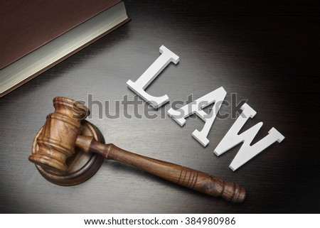 Top View Of Judges Gavel, Red Book And White Sign Law On The Black Wood Background, Conceptual Image