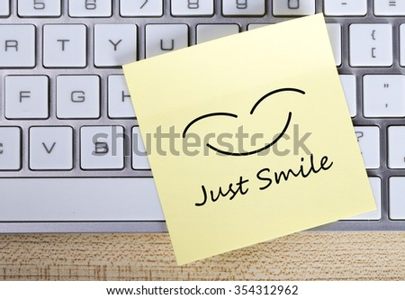 Top view of Just Smile sticky note pasted on the keyboard. - stock photo