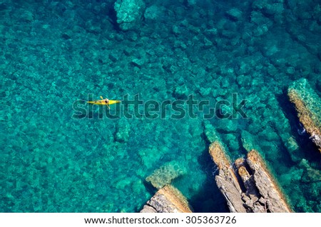 Top view of kayak boat oin shallow turquoise water of Ligurian sea, Italy - stock photo