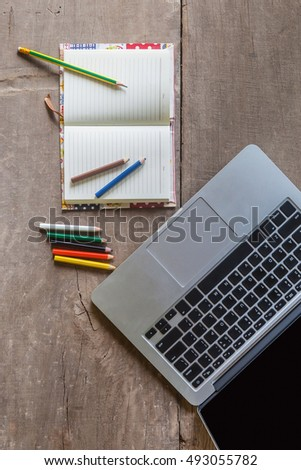 Top view of laptop and blank notebook with color pencils on wooden floor