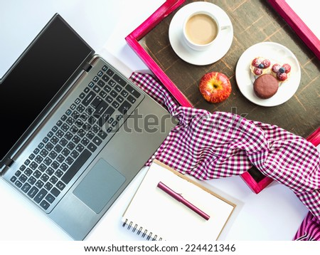 Top view of laptop computer with a wooden tray of light meal - stock photo