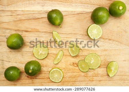 Top view of limes on the wooden board  - stock photo