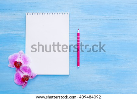 Top view of Lined note paper with pencil on blue wood table for background with orchids. white notebook. pocketbook. Pink pen   - stock photo