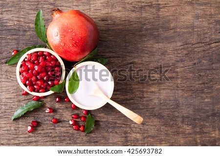 Top view of lotion in bowl with fresh pomegranate seeds on wooden table top - stock photo