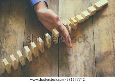 top view of male hand placing wooden block on a tower. planing and strategy concept. vintage filtered  - stock photo