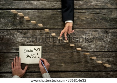 Top view of male hand writing an encouraging message Dream big in a notepad as a businessman walks his fingers up wooden pegs resembling staircase.  - stock photo