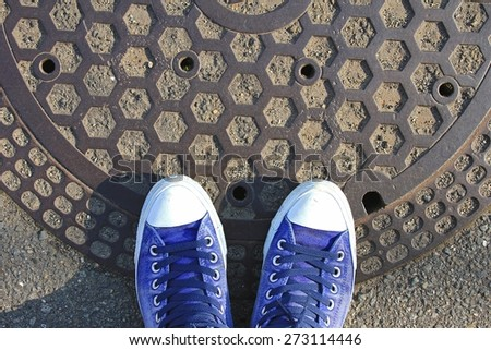 Top view of male sneakers on round steel sewer manhole on pavement in Japan. - stock photo