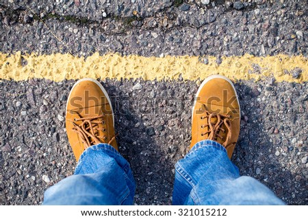 Top view of male sneakers on the asphalt road with yellow line.  - stock photo