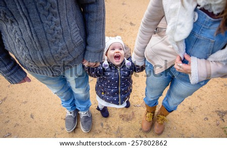 Top view of man and woman holding hands of smiling and happiness little girl with a funny hat outdoors. Family leisure outdoors concept. - stock photo