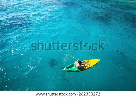 top view of man paddling on kayak in turquoise water - stock photo