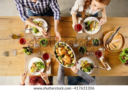 Top view of man passing food bowl to friend. High angle view of happy young friends eating together at home. Happy men and women having lunch with roasted chicken. - stock photo