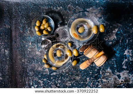 Top view of martini glasses at bar. Long cocktail drinks, alcoholic beverages with vodka, olives and ice - stock photo