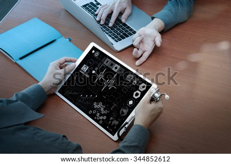 top view of Medicine doctor hand working with modern computer and digital pro tablet with digital medical diagram with his team on wooden desk as medical concept - stock photo