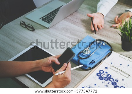 top view of Medicine doctor hand working with modern computer and digital tablet and smart phone with blank screen with his team on wooden desk as medical concept - stock photo