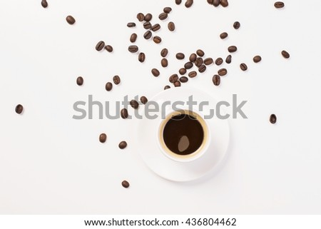 Top view of messy white surface with coffee cup on ceramic saucer and beans - stock photo