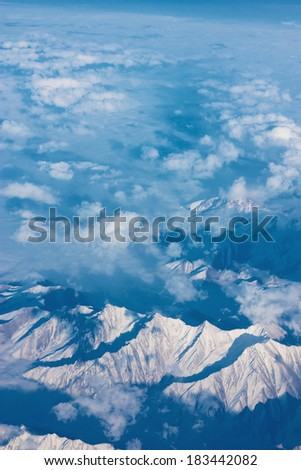 Top view of mountains with snow and clouds. - stock photo