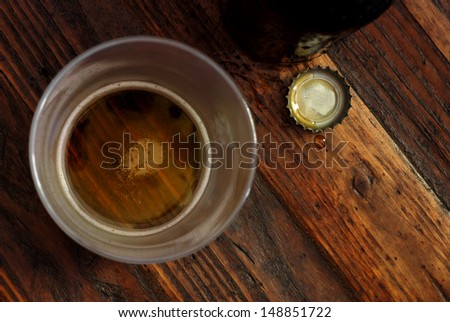 Top view of near empty beer glass with bottle cap and bottle on rustic wood background.  Low key still life with directional natural lighting for effect.  Selective focus on bottle cap and droplet. - stock photo