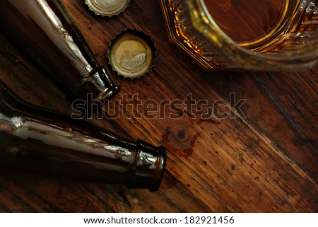 Top view of near empty beer glass with bottle caps and bottles on rustic wood background. Low key still life with directional natural lighting for effect. Selective focus on bottle caps and droplets.  - stock photo