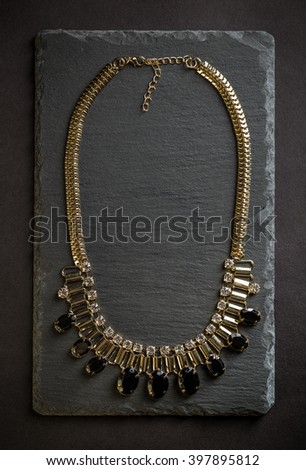 Top view of necklace with black stones on black slate background