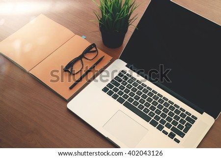 top view of new modern computer laptop with blank screen and blank book with eye glass as concept - stock photo