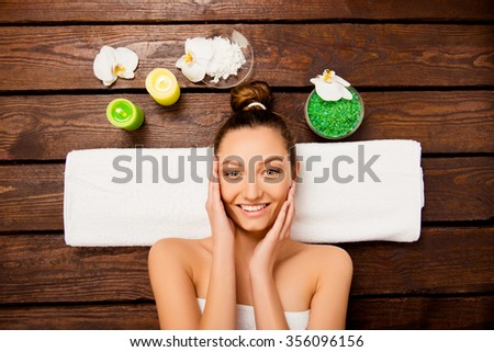 Top view of nice young woman laying in spa salon relaxing touching face - stock photo