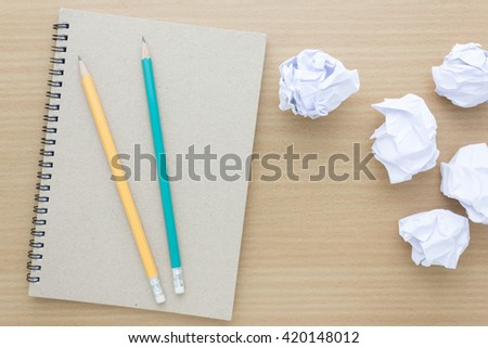 Top view of notebook with crumpled paper ball and pencil - stock photo