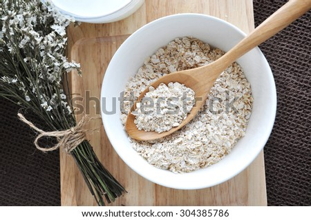 top view of oat in wooden spoon put in white bowl - stock photo