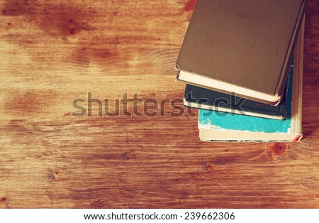 top view of old book stack over wooden table. filtered image - stock photo