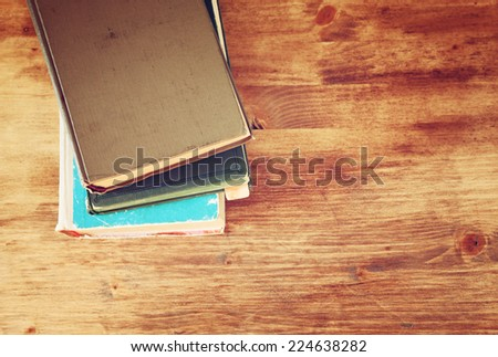 Top view of old books on a wooden table. retro filtered image room for text - stock photo