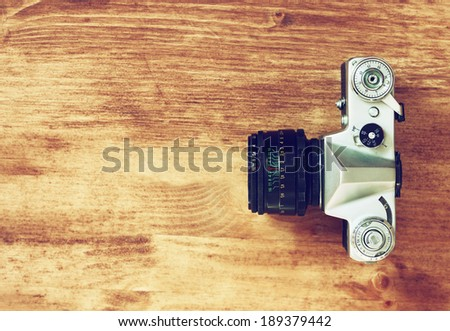 top view of old camera over wooden table. retro filter. - stock photo