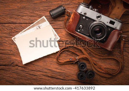 top view of old fashioned photo camera with photo cards on wooden background - stock photo