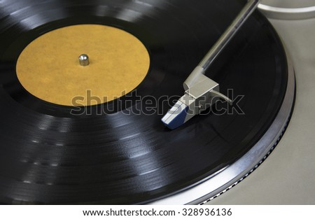 Top view of old fashioned turntable playing a track from black vinyl. Copy space for text. Vinyl record with yellow label playing on a turntable. Overview shot - stock photo
