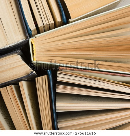 Top view of old used hardback books. Open book, fanned pages. Back to school. Reading are essential for self improvement, gaining knowledge and success in our careers, business and personal lives. - stock photo