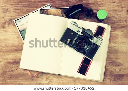 top view of old vintage camera and pictures over wooden brown background. vintage effect process.  - stock photo
