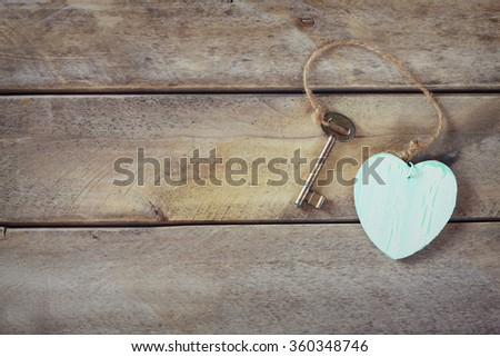 top view of old vintage key with a wooden heart on wooden background - stock photo