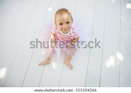 Top view of One year old baby girl on wooden withe floor