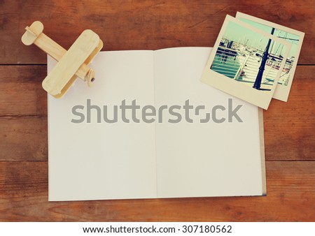 top view of open blank notebook and travel polaroid photographs next to cup of coffee over wooden table. ready for mockup. retro filtered image  - stock photo