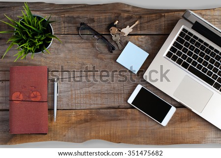 Top view of open laptop, smart phone, glasses, notebook and keys. Workspace background - stock photo