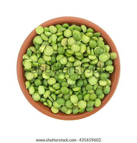 Top view of organic green split peas filling a small bowl isolated on a white background. - stock photo
