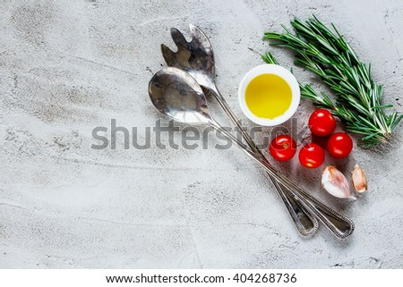 Top view of organic vegetables cooking ingredients with rosemary, olive oil and tomatoes over grey concrete background, place for text, border. Healthy lifestyle or detox diet food concept. - stock photo