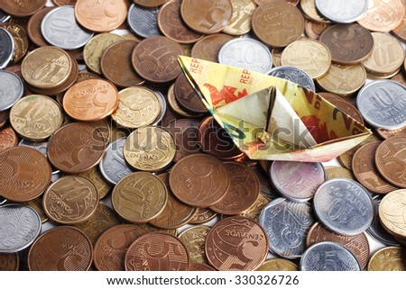 Top view of origami boat made of brazilian money with coins. - stock photo