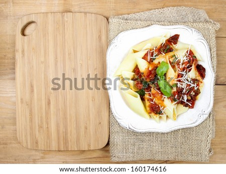 Top view of penne with dried tomatoes. Italian cuisine, delicious, popular dish. - stock photo