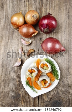 Top view of pickled herring rolls with vegetables on brown wooden background. Fresh onions and garlic, copy space. - stock photo