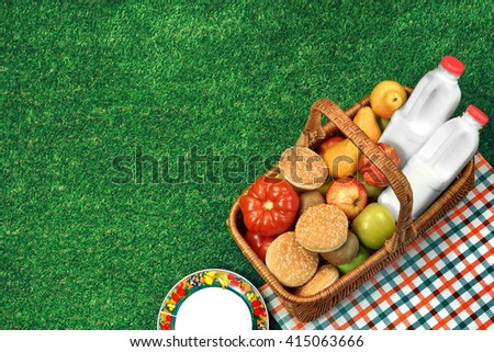 Top View Of Picnic Scene. Wicker Basket With Healthy Food And Drinks And Checkered Cloth On The Fresh Park Lawn - stock photo